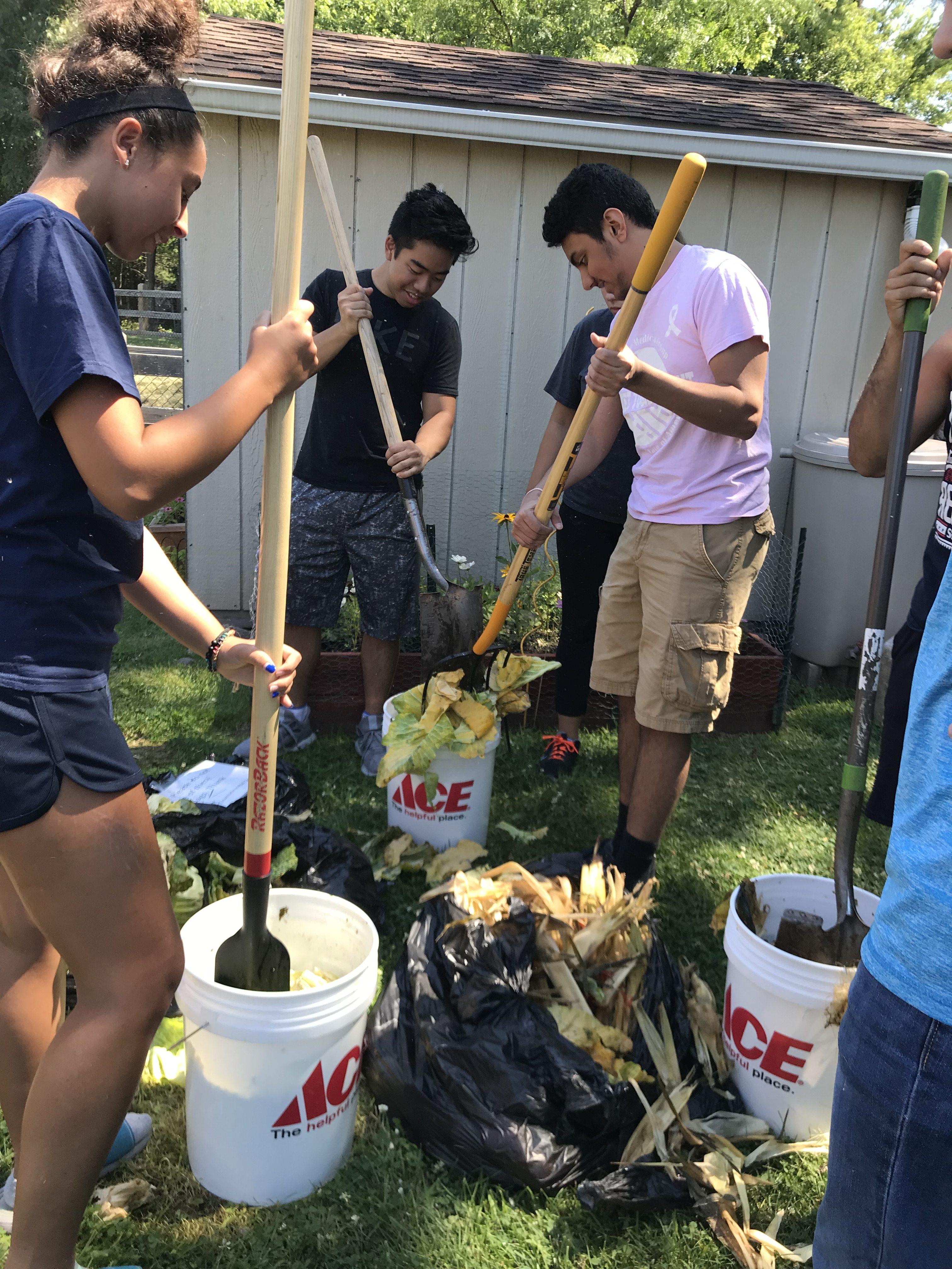 Participants chop food scraps to facilitate decomposition.